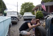 """Dan Wagner shows his daughter, Jessica, 11, the rusted pin he was trying to knock out of an old Mercury at his home July 11. Wagner is losing a slice of his property to Portland-Milwaukie light rail — the future MAX Orange Line — and says he might have to move to continue his work restoring cars. """"Without the driveway, I can't do this,"""" Wagner said. """"And it's one of the reasons I bought the house."""""""